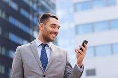 与智能手机的微笑的商人户外 免版税库存照片