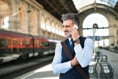 与智能手机的成熟商人在火车站 库存图片