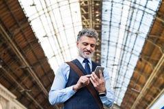 与智能手机的成熟商人在火车站 免版税库存图片