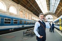 与智能手机的成熟商人在火车站 免版税库存照片