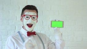 与智能手机的笑剧在手中在绿色背景中 手势 影视素材