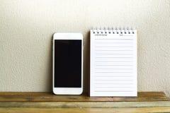 与智能手机的笔记薄在木头和墙壁背景 使用教育的墙纸,企业照片 注意到暴民的产品 库存照片