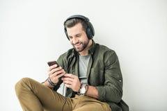 与智能手机的英俊的微笑的人听的音乐 免版税库存照片