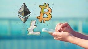 与智能手机的Bitcoin Ethereum和Litecoin 库存图片