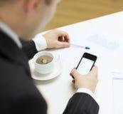 与智能手机读书新闻的商人 图库摄影