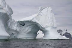 与曲拱的冰山在反对背景的南极水域中  免版税图库摄影