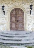 与曲拱的木门在石墙上 库存照片