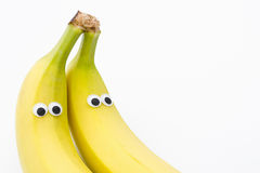 与曲棍球的眼睛的香蕉在白色背景-香蕉面孔 图库摄影