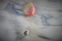 与更小的石头的红色和黄色岩石在海滩 库存照片