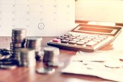 与最后期限日历的收债和税季节概念提醒笔记,硬币,银行,在桌上的计算器 库存图片