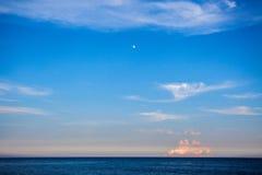 与月亮和云彩的风景蓝色海洋或海视图 图库摄影