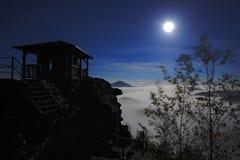与月亮的夜在监视 在谷的白色雾 在夜期间,在石小山的城楼 背景美好的图象安装横向晚上照片表使用 小山和vil 库存照片