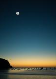 与月亮的日落海湾 免版税库存图片