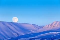 与月亮,蓝色冰川斯瓦尔巴特群岛,挪威的白色多雪的山 冰在海洋 在北极的冰山微明 与冰的桃红色云彩 免版税库存照片
