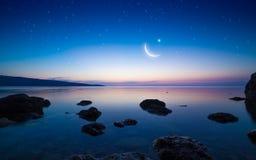 与月牙的斋月Kareem在平静的海上的背景和星 图库摄影