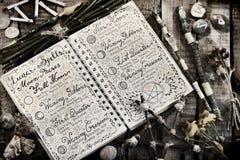 与月球咒语、诗歌、五角星形和魔术鞭子的旧书在板条,定了调子图象 库存图片