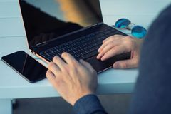 与有一个手机的一台个人计算机膝上型计算机一起使用附近在晴朗的d 库存照片