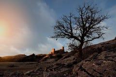 与有些山和城堡o的日落风景 库存图片