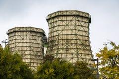 与有些树的两个老冷却塔在前面 免版税库存照片