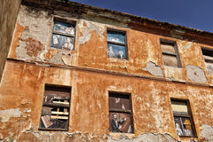 与有些绘画的老破裂的门面在窗口盖子 免版税库存图片