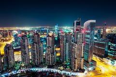 与有启发性摩天大楼的意想不到的夜间迪拜地平线 免版税图库摄影