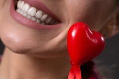 与有吸引力微笑和白色牙的红色心脏 免版税库存图片