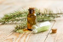 与有机云杉的油和海盐的温泉在木桌背景的玻璃瓶 免版税库存图片