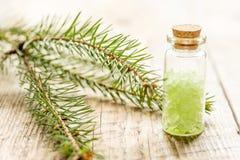与有机云杉的海盐的温泉在木桌背景的玻璃瓶 免版税库存图片