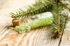 与有机盐的云杉的温泉在木桌背景的瓶 库存照片