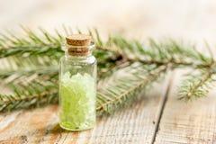 与有机盐的云杉的温泉在木桌背景的瓶 免版税库存照片