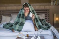 与有的组织的病的在家被浪费的和被用尽的人床说谎的感觉不适的遭受的寒冷和流感打喷嚏的鼻子病毒和 库存图片