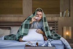 与有的组织的病的在家被浪费的和被用尽的人床说谎的感觉不适的遭受的寒冷和流感打喷嚏的鼻子病毒和 图库摄影