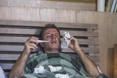 与有的组织的病的在家被浪费的和被用尽的人床说谎的感觉不适的遭受的寒冷和流感打喷嚏的鼻子病毒和 免版税图库摄影