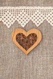 与有花边的布料和木心脏的粗麻布背景 免版税图库摄影