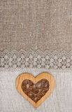 与有花边的布料和木心脏的粗麻布背景 库存图片