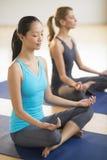 与朋友的女子实践的瑜伽健身俱乐部的 免版税库存图片