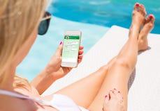 与朋友的妇女传讯她的智能手机的 免版税库存照片