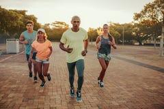 与朋友的适合的年轻人奔跑 免版税图库摄影