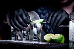 与朋友酒吧的,三杯酒精与石灰和盐的开胃酒装饰的 龙舌兰酒射击,有选择性 免版税库存图片