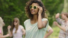 与朋友,池边聚会的年轻无忧无虑的学生的逗人喜爱的两种人种的女孩跳舞 股票录像