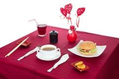 与服务的桌的表与早餐和饮料,桌布红色,利器 关闭,室内 免版税库存照片