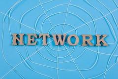 与木信件的词网络以一个抽象蜘蛛网,蓝色背景的形式 免版税图库摄影