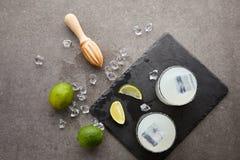 与木剥削者、刷新的酸caipirinha鸡尾酒与石灰和冰的平的位置在灰色桌面 库存照片