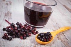 与木匙子和汁液的新鲜的接骨木浆果在老木背景,健康营养 免版税库存图片