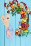 与木匙子和绞拌器的新鲜的有机菜在蓝色背景 文本的空间 免版税库存图片