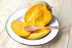 与木匙子的可口成熟芒果果子在木背景的更加白色的盘 库存图片