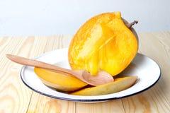 与木匙子的可口成熟芒果果子在木背景的更加白色的盘 免版税库存照片