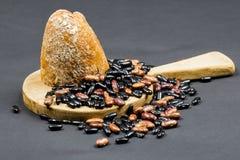 与木厨房切板的静物画构成、黑和棕色豆和有机面包 库存照片