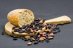 与木厨房切板的静物画构成、黑和棕色豆和有机面包 免版税库存图片
