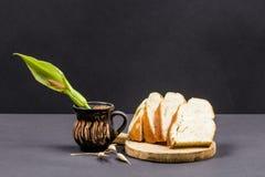 与木厨房切板的静物画构成,萝卜种子、面包和陶瓷罐有Arum的开花 库存图片